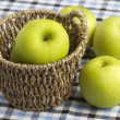Three green apples on the table and one in basket  — Stock Photo