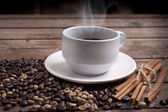 Coffee cup and saucer on a wooden table. Dark background. — Stock Photo