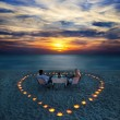 A young couple share a romantic dinner on the beach -  