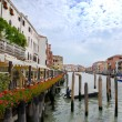 Venice channel and seafront with red flowers, Italy - Photo