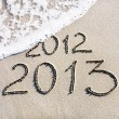 Happy New Year 2013 replace 2012 concept on the sea beach — Stock Photo #22460557