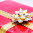 Single red gift box with golden ribbon and the close up of white - Stock Photo