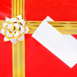 Single red gift box with golden ribbon and the close up of white — Stock Photo #22460797