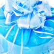 Festive packed blue nacreous present with big bow isolated on wh - Stock Photo