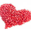 Ripe pomegranate seeds in form of heart isolated on white backgr — Stock Photo