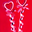 Two red valentine hearts with bows against red background — Stock Photo