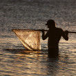 Fisherman with the landing net at sunset sea way — Stock Photo