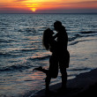 Couple silhouette on beach against sunset — Stock Photo #22462051