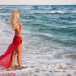 Blonde woman in red skirt on the sea beach — Stock Photo