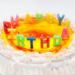 Appetizing birthday cake with the light rainbow letter candles w — Stock Photo #22462065