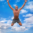 Young man jumping in the air against a blue sky — Stock Photo
