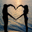 Young couple making shape of heart with arms on beach against su — Stock Photo #22462161