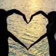 Young couple making heart shape with arms on beach against sunse - Foto Stock