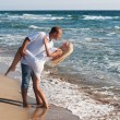 Loving couple dancing on the sea beach at summer - Stock Photo