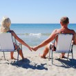 Young couple sitting on the beach chair on the sea beach and loo — Stock Photo