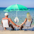 Young couple sitting on the beach chairs under the green beach u — Stock Photo #22462351