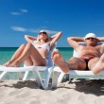Young couple sunbathe on the beach bed on the sea beach — Stock Photo #22462599