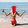 Beautiful woman in santa hat on the sand sea shore — Stock Photo