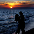 Couple silhouette on beach against sunset — Stock Photo #22462761
