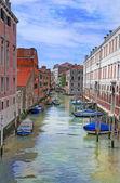 Venice canal with gondolas, boats and small bridge. Italy — Stock Photo