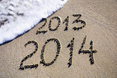 Happy New Year 2014 replace 2013 concept on the sea beach — Stok fotoğraf