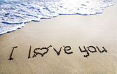 """Words """"I love you"""" outline on the wet sand with the wave brillia — ストック写真"""
