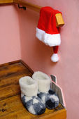 Red santa hat and warm woolen boots at home interior - christma — Stockfoto
