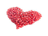 Ripe pomegranate seeds in form of heart isolated on white backgr — Stockfoto