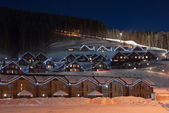 Night view of downhill skiing - small attractive hotels with lights against the pinewood and ski lift — Stock Photo