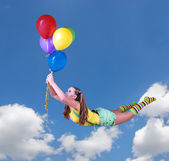 Young pretty girl fly on colorful balloons in the blue sky — Stock Photo