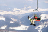 Snowboarder on a ski lift — Foto Stock