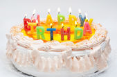 Appetizing birthday cake with the light rainbow letter candles w — Stock Photo