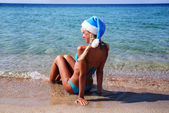 Beautiful woman in santa hat on the sea shore - winter holiday i — Stock Photo