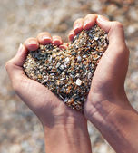 Hands holding a sand in form of the heart — Stock Photo