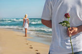 Loving couple, man with rose waiting his woman on the sea beach — Stok fotoğraf