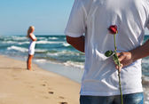 Loving couple, man with rose waiting his woman on the sea beach — Zdjęcie stockowe