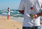 Pareja amorosa, hombre con rosa espera a su mujer en la playa del mar — Foto de Stock