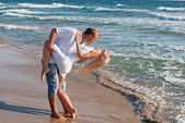 Loving couple dancing on the sea beach at summer — Stock Photo