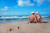 Loving couple sitting on the sea sand beach and look at each oth — Stock Photo