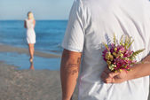 Loving couple - man with flower bouquet waiting his woman on the — Stock Photo