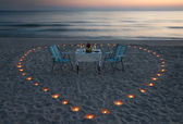 Romantic dinner on the sea beach with candle heart — Stock Photo