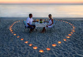 A young lovers couple share a romantic dinner with candles heart — Stockfoto