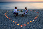 A young lovers couple share a romantic dinner with candles heart — Stock fotografie