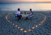 Un couple de jeunes amoureux partager un dîner romantique avec coeur de bougies — Photo