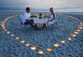 A young lovers couple share a romantic dinner with candles heart — Zdjęcie stockowe