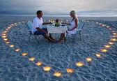 Pár mladých milenců sdílet romantickou večeři s svíčky srdce — Stock fotografie