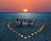 A young couple share a romantic dinner on the beach — Foto Stock
