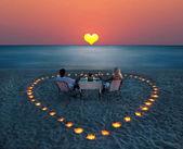 Młoda para podziel romantyczną kolację na plaży — Zdjęcie stockowe