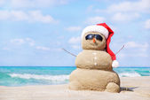 Smiling sandy snowman in red santa hat on the sea beach. — Stock Photo