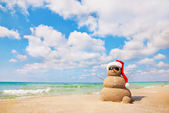 Sand snowman in santa hat. Holiday concept can be used for New Y — Stock Photo